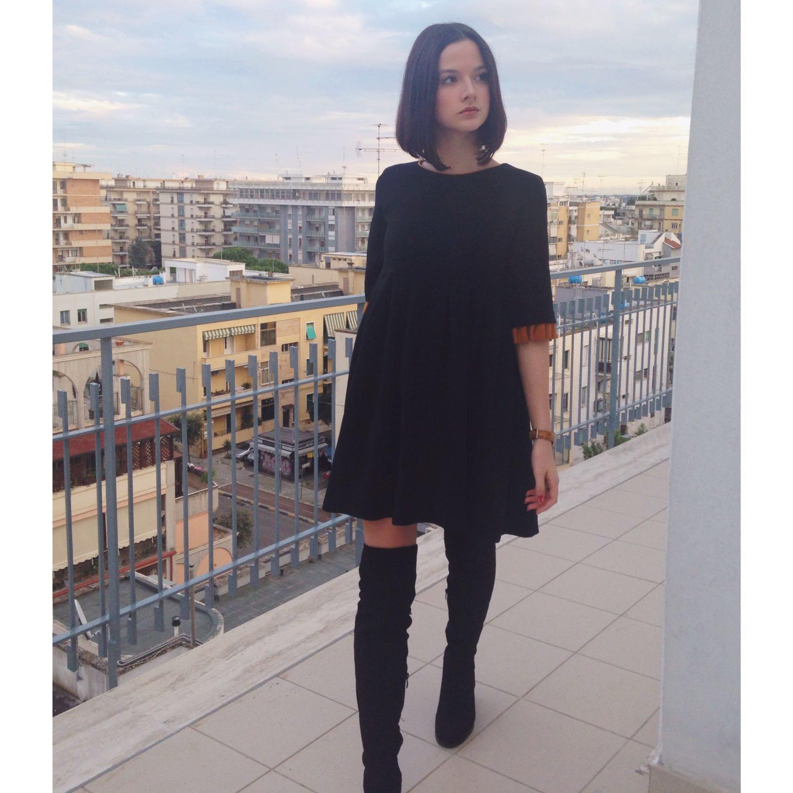 scelto questo outfit un vestito nero con degli stivali alti fino al  ginocchio, il vestito non è semplicemente nero ma alla fine delle maniche  presenta